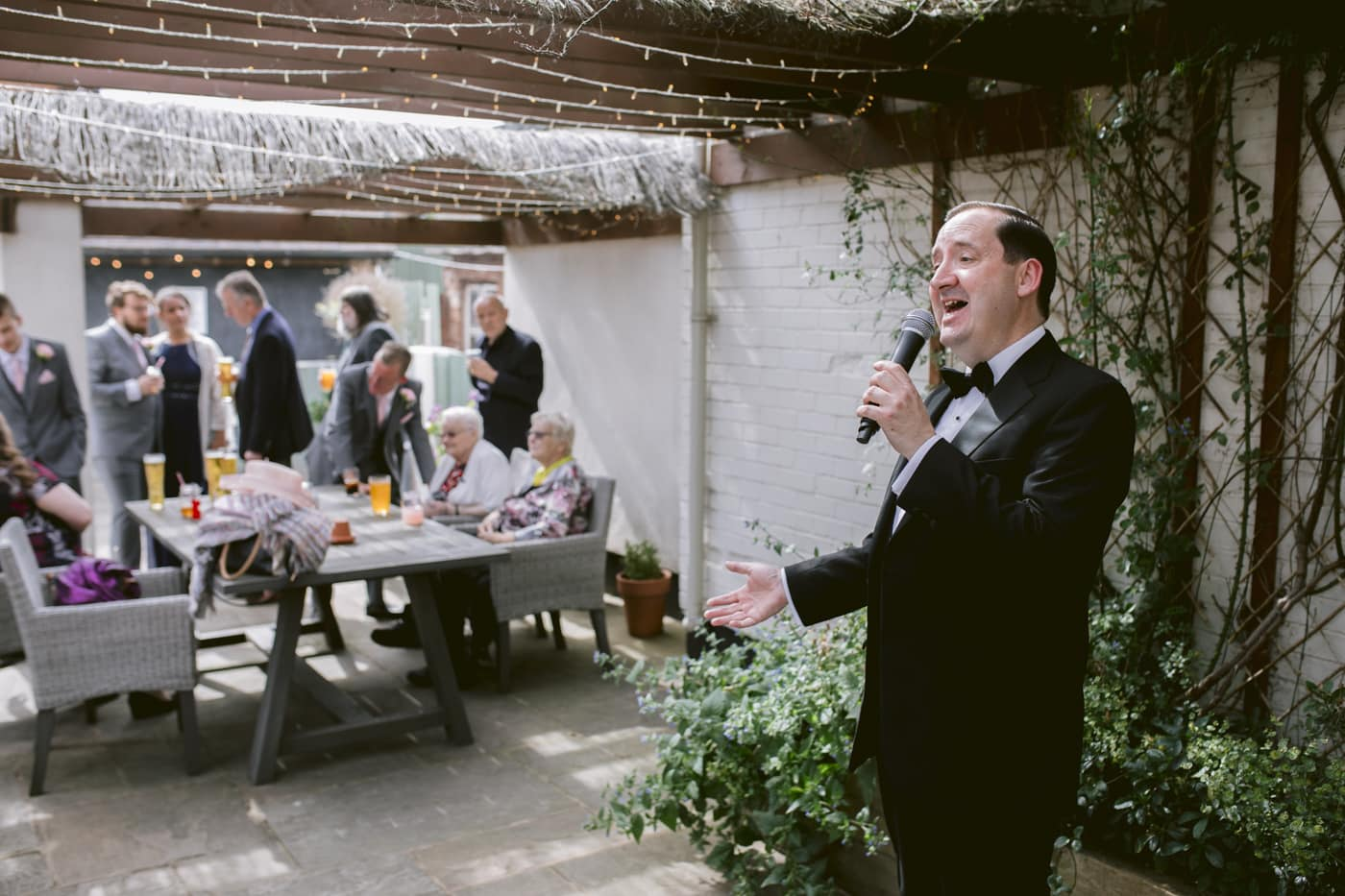Man in Suit Singing with Guests in the Background Photography
