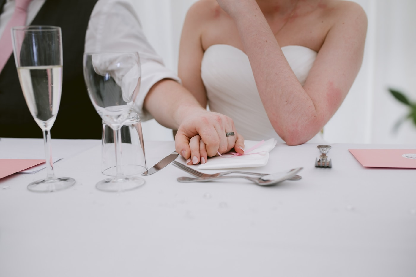 Bride and Groom Sitting at Table Holding Hands in Union Portrait