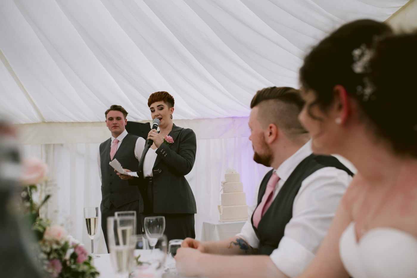 Bride and Groom at Table with Glasses listening Guest Speeches