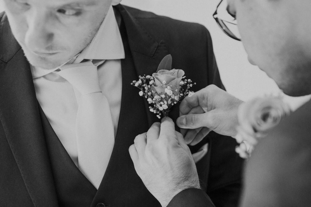Additional Photographer Photograph at Groom Prep of button hole being put on