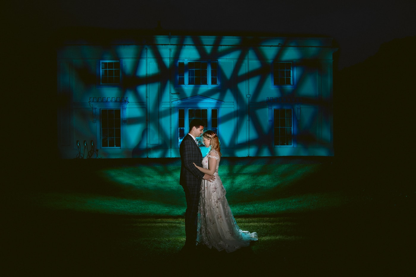 Bride and Groom Bathed in Light on Front of House at Storrs Hall Wedding