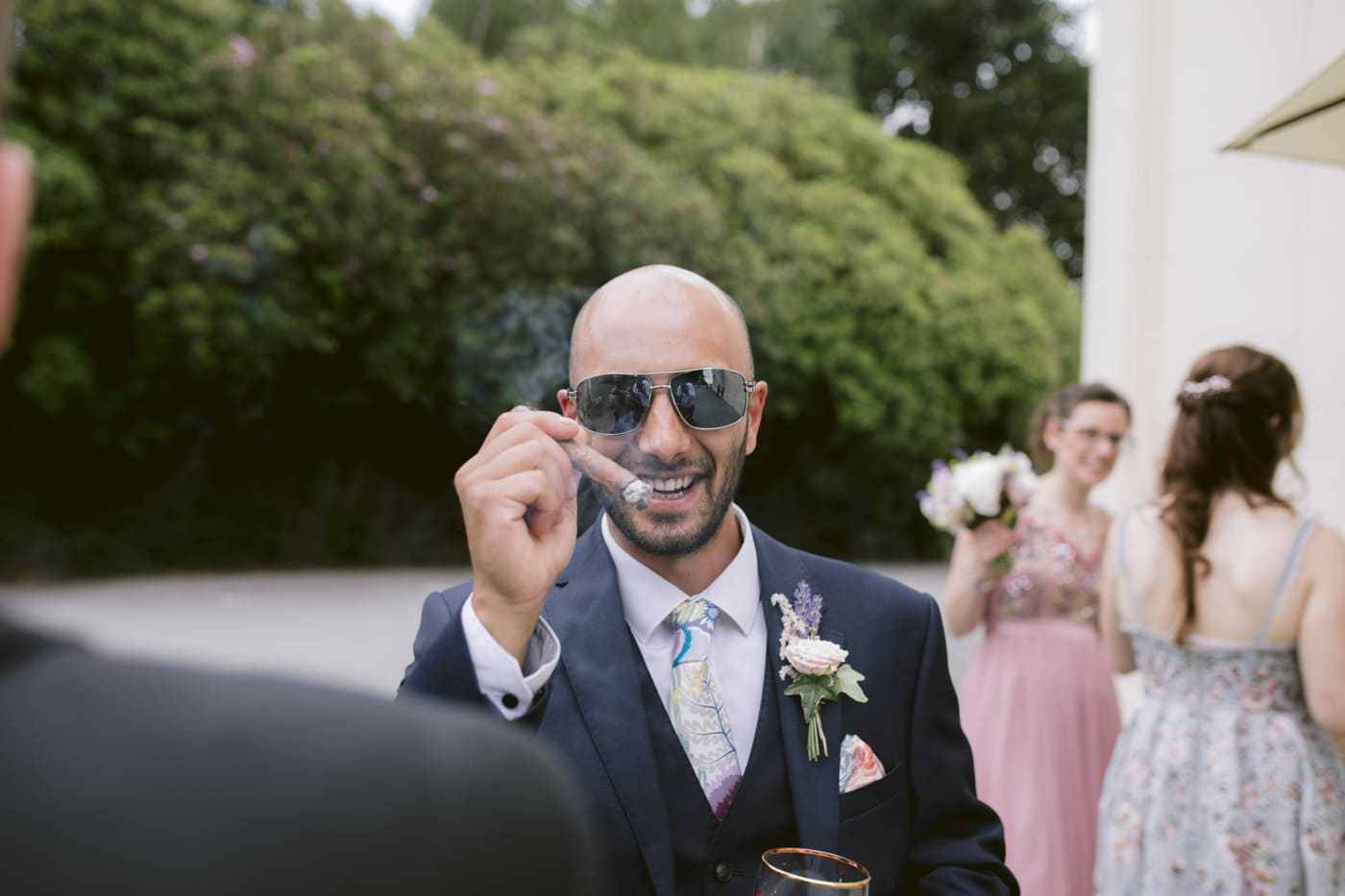 Man with Cigar and Glasses Outside with Guests at Storrs Hall Wedding