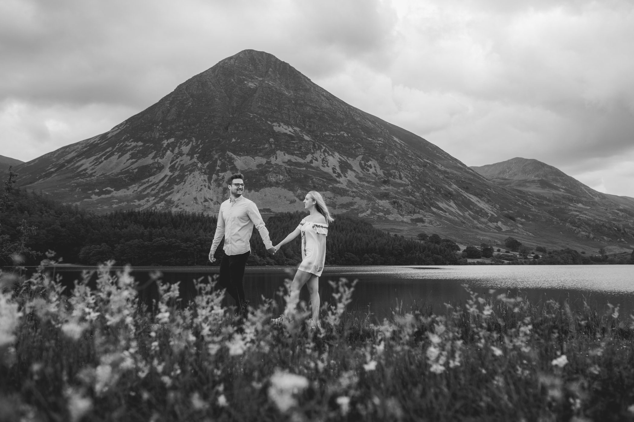 Couple walking hand in hand at Crummock Water for a portrait session