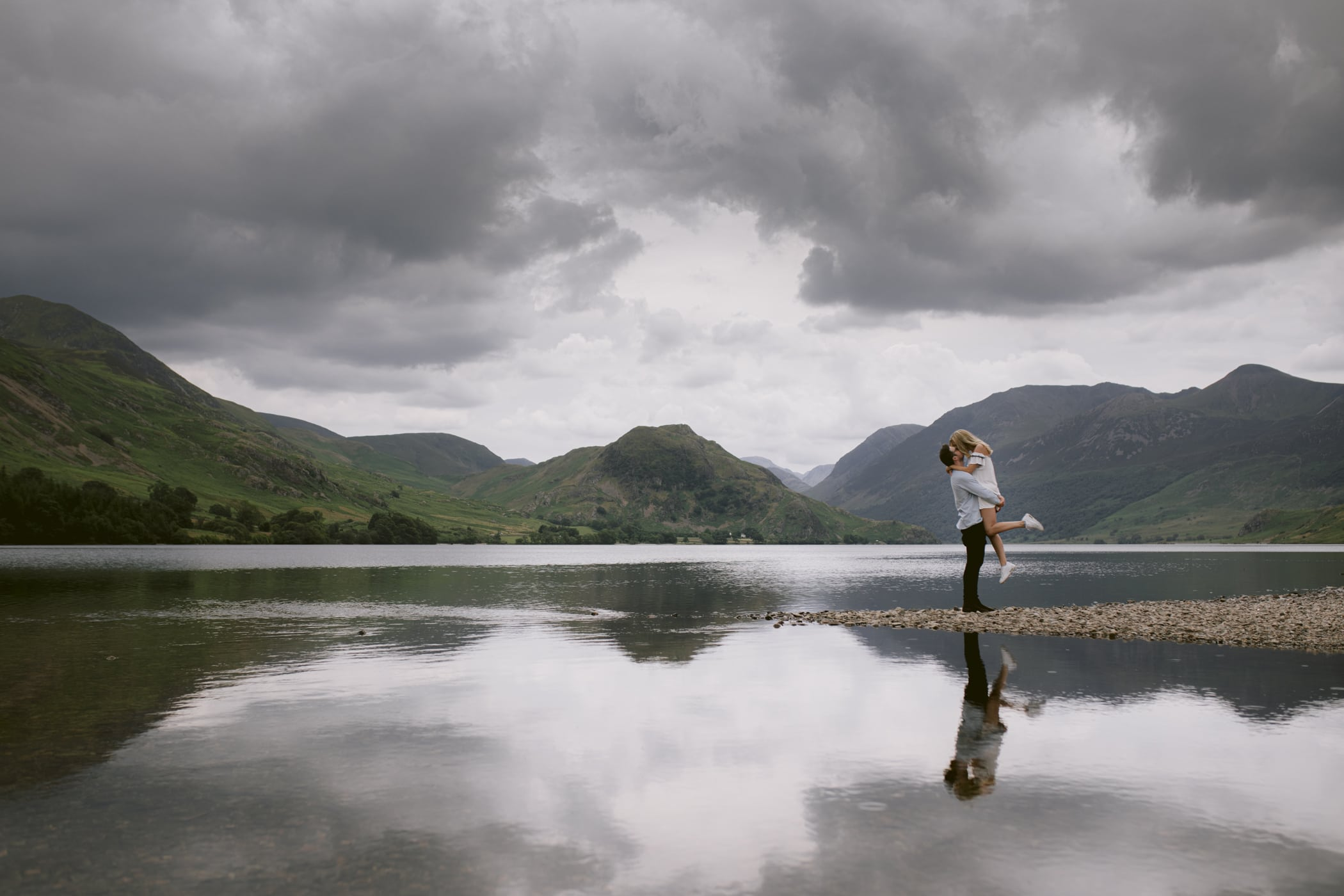 Couple together at Crummock water, jumping in each other arms, lakes side shot