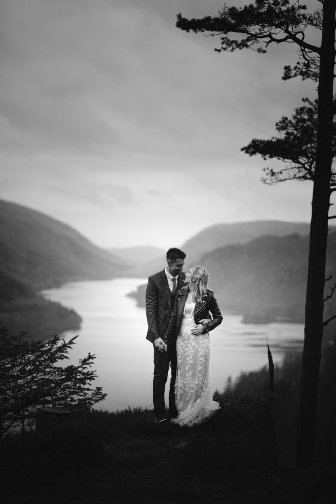 Bride and Groom who eloped in the Lake District standing near Raven Crag  overlooking a lake